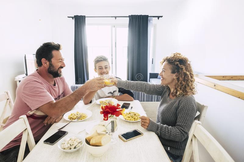 Happy people caucasian family with mom dad and son eatiign together at home in a white bright room - ordinary real life for royalty free stock photos