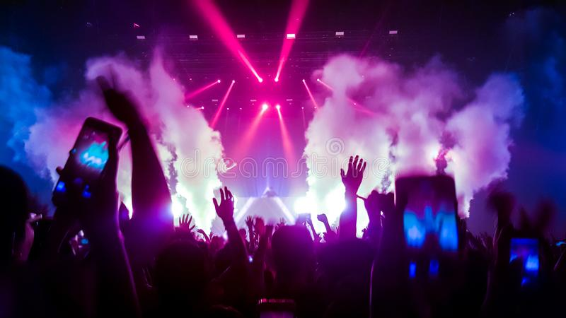 Happy People Dance in Nightclub Party Concert. And listen to music from DJ on the stage in background. Cheerful crowd celebrate Christmas and New Year party royalty free stock images