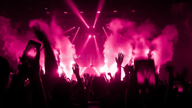 Happy People Dance in Nightclub Party Concert. And listen to music from DJ on the stage in background. Cheerful crowd celebrate Christmas and New Year party stock photo
