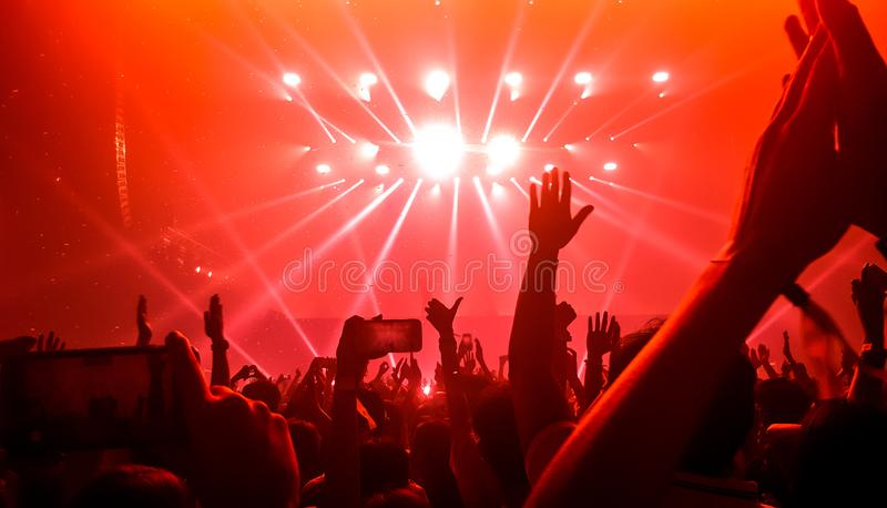 Happy People Dance in Nightclub Party Concert. And listen to music from DJ on the stage in background. Cheerful crowd celebrate Christmas and New Year party stock photography