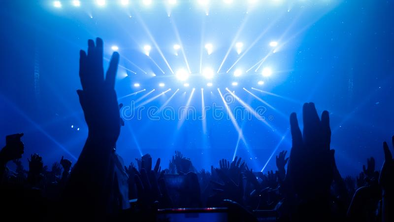 Happy People Dance in Nightclub Party Concert. And listen to music from DJ on the stage in background. Cheerful crowd celebrate Christmas and New Year party royalty free stock photos