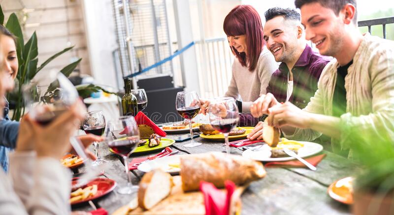 Happy people drinking wine together at rooftop party in open air villa - Young friends eating food at restaurant patio royalty free stock images