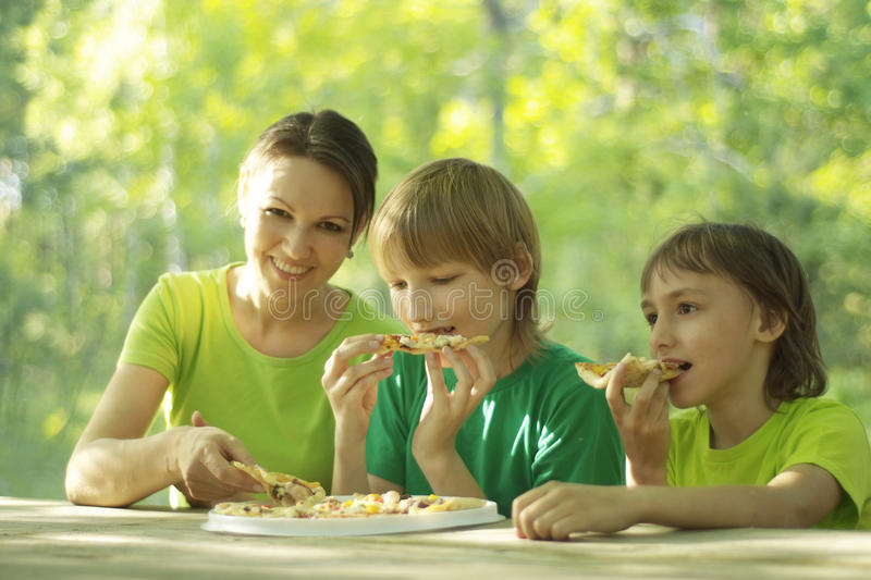 Happy people eat pizza. Happy cute family eat pizza together outdoors royalty free stock image