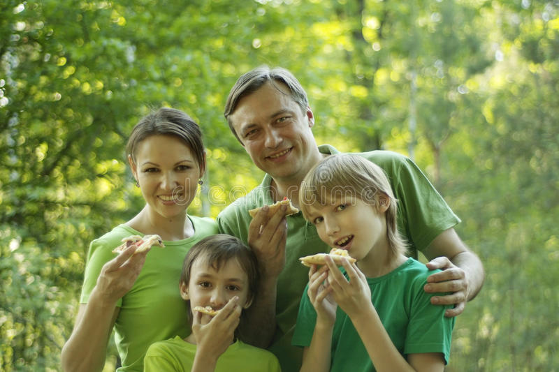 Happy people eat pizza. Happy smiling family eating pizza in the park stock images