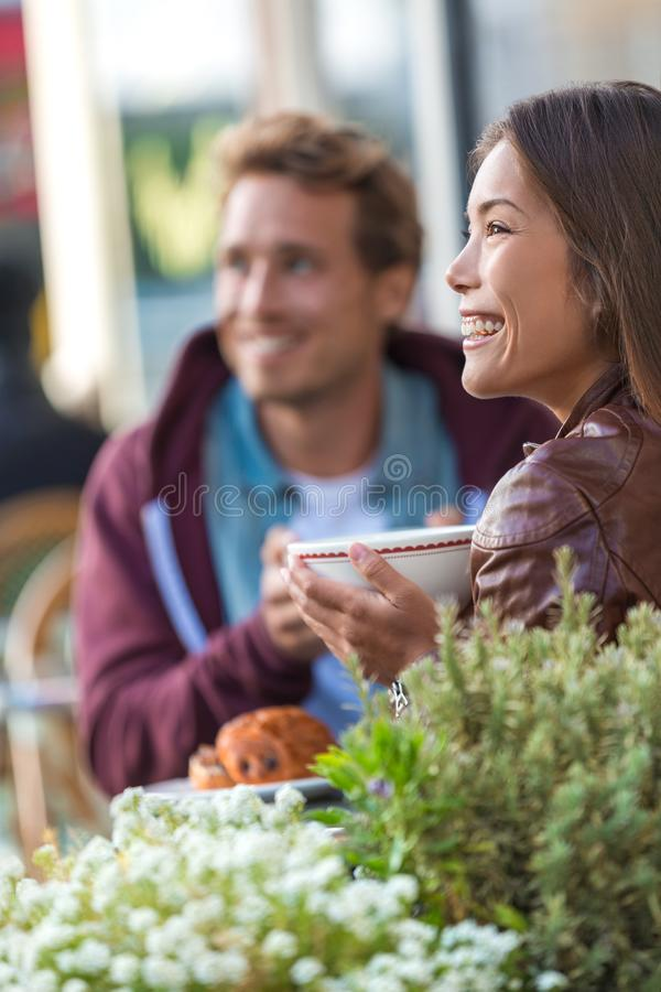 Happy people eating brunch at cafe. Young couple hipsters drinking coffee at restaurant table outside sidewalk terrace at parisian stock image