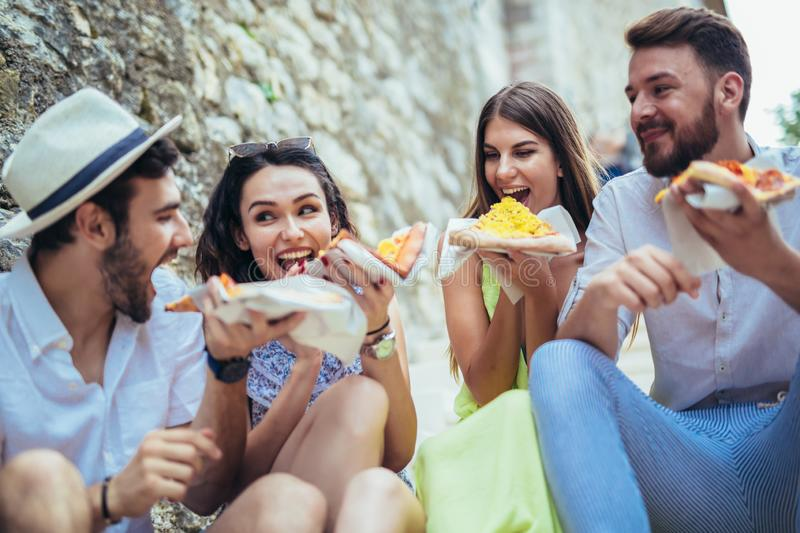 People eating fast food in city while travelling. Happy people eating fast food in city while travelling royalty free stock images