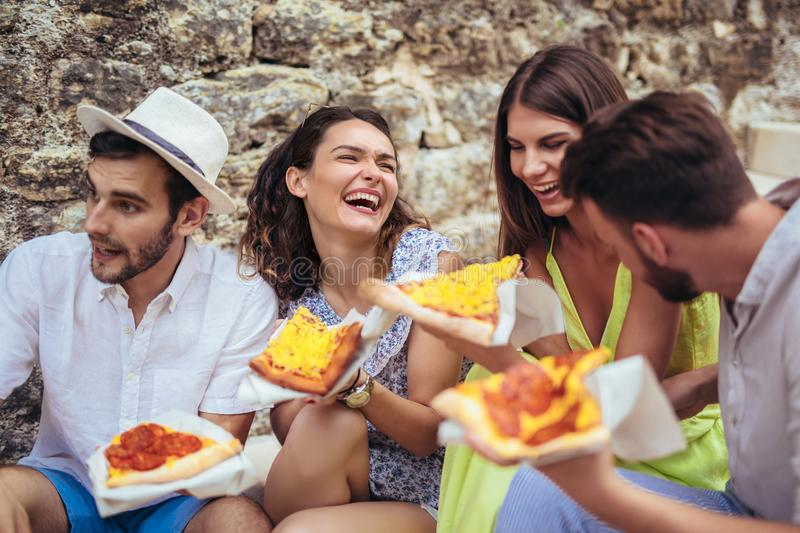 Happy people eating fast food in city while travelling. Happy tourist people eating fast food in city while travelling royalty free stock image