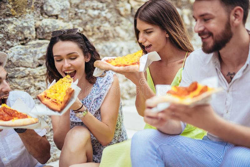 Happy people eating fast food in city while travelling. Happy tourist people eating fast food in city while travelling stock photography