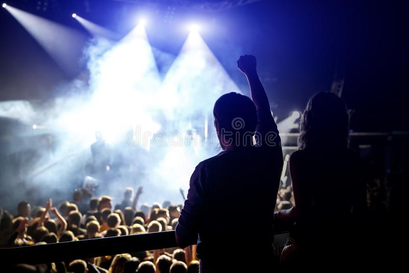 Happy people enjoying rock concert, raised up hands and clapping of pleasure, active night life concept stock photos