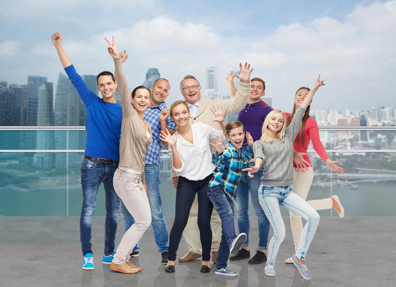 Happy people having fun over city waterside. Family, gender, generation and people concept - group of happy men, women and boy having fun and waving hands over stock photography