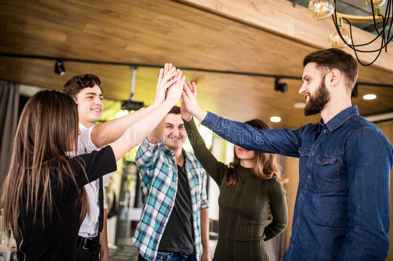 Happy people high fiving each other at meeting or seminat of teamwork in office stock images