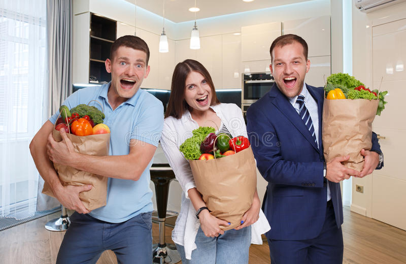 Happy people hold bags with healthy food, grocery buyers royalty free stock photography