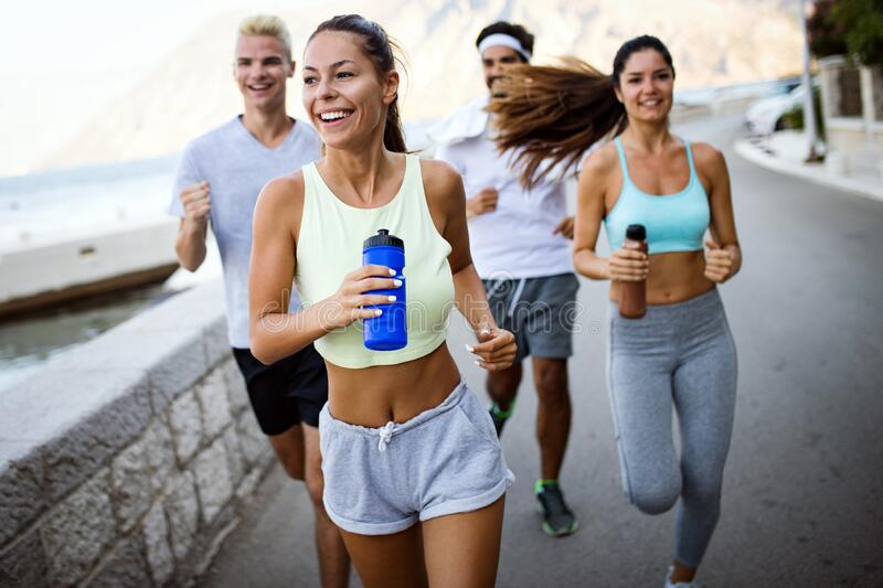 Happy people jogging outdoor. Running, sport, exercising and healthy lifestyle concept royalty free stock photography