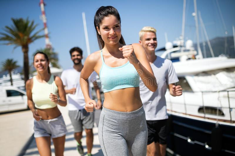 Running, friends, sport, exercising and healthy lifestyle concept. Happy people jogging outdoor. royalty free stock photos