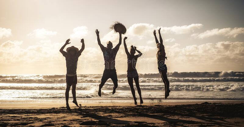 Happy people jump with joy and happiness during summer holiday vacation together in friendship having fun - silhouettes young stock photos