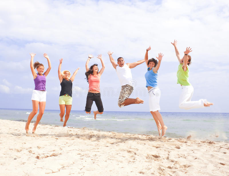 Happy people jumping on the beach royalty free stock image