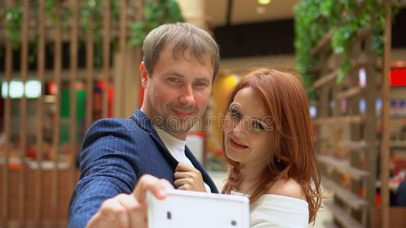 Happy people make selfies. Lovely woman enjoying shopping at the mall with her boyfriend stock photography