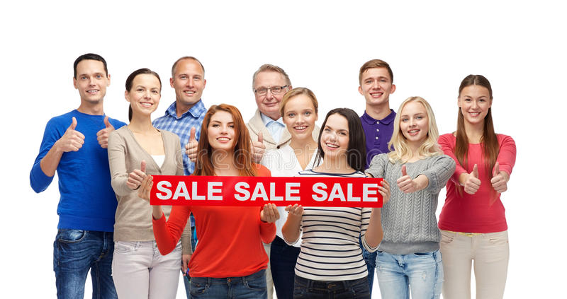 Happy people with red sale sign showing thumbs up. Gesture, shopping, advertisement and people concept - group of smiling men and women showing thumbs up and stock images