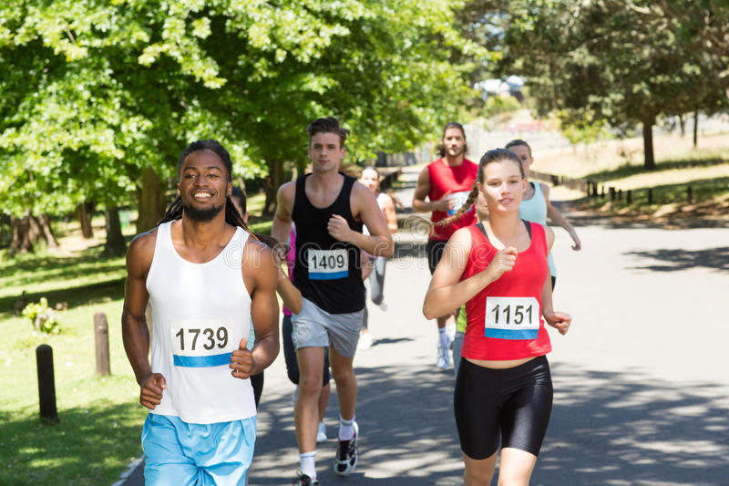 Happy people running race in park stock image