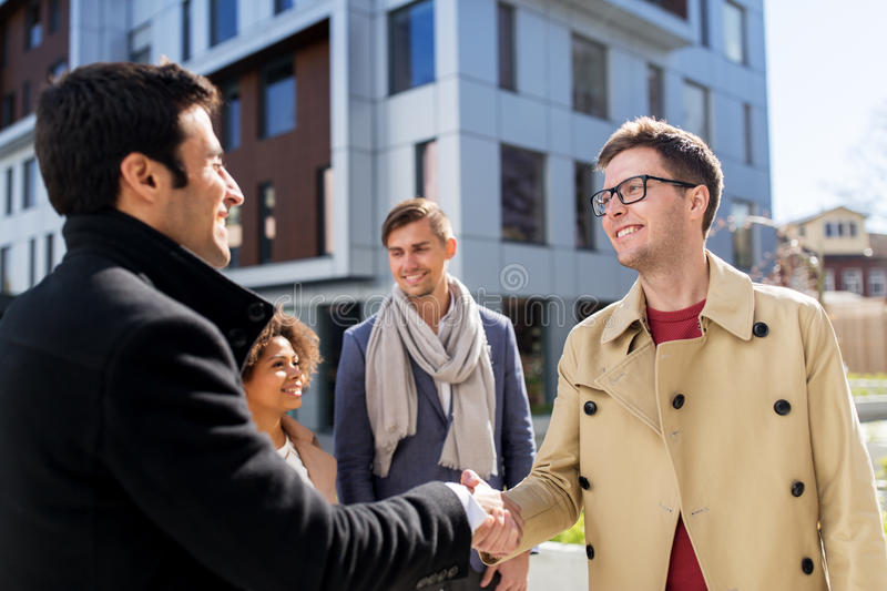 Happy people shaking hands on city street royalty free stock photography