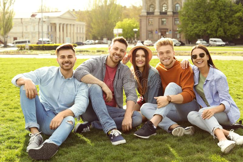 Happy people sitting on green grass stock photo