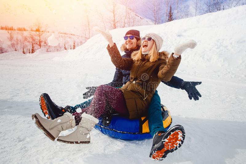 Happy people on tube outdoors in mountains in winter snow stock image