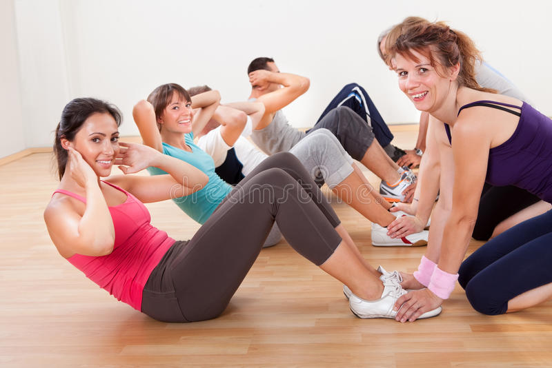 Happy people working out in a gym stock images