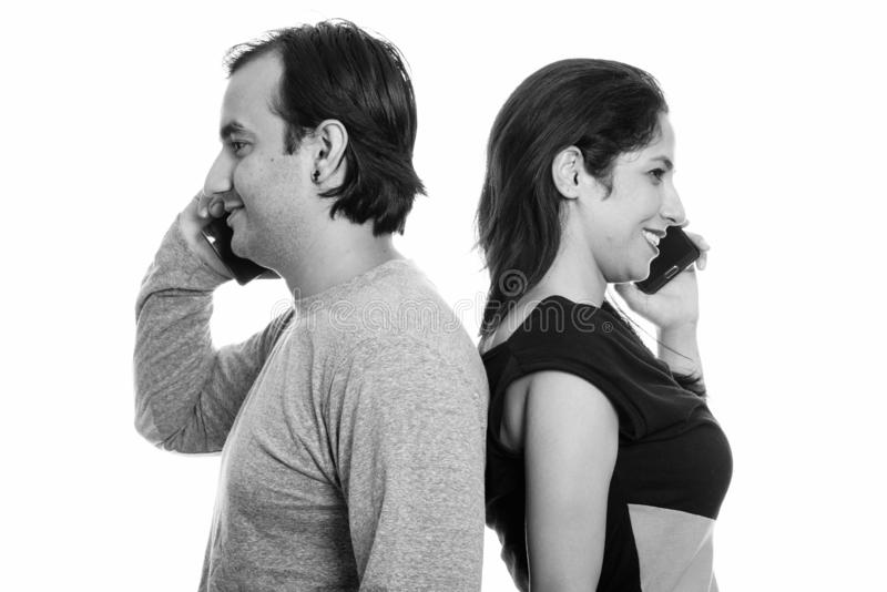 Happy Persian couple smiling while talking on mobile phone together back to back royalty free stock photo
