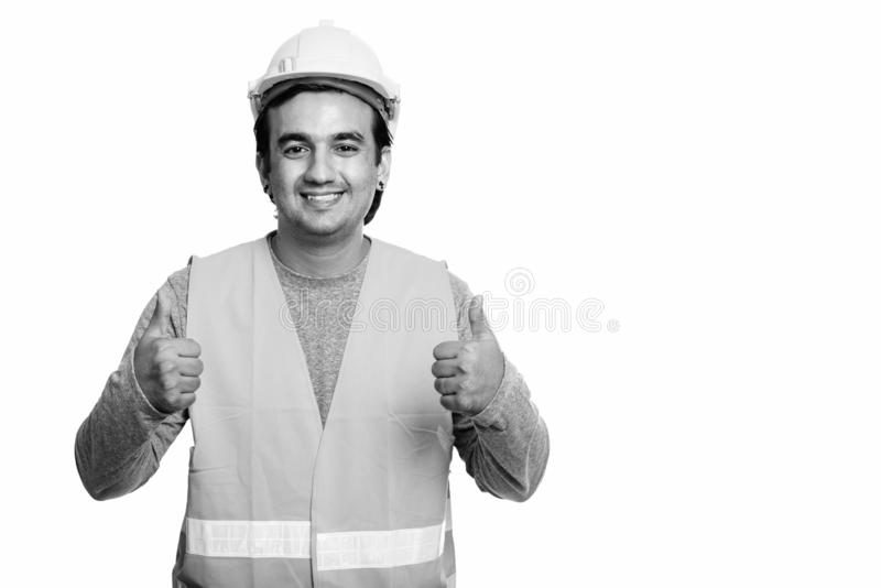 Happy Persian man construction worker smiling while giving thumbs up. Studio shot of Persian man construction worker isolated against white background in black royalty free stock images