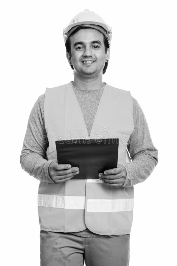 Happy Persian man construction worker smiling while holding clipboard royalty free stock images