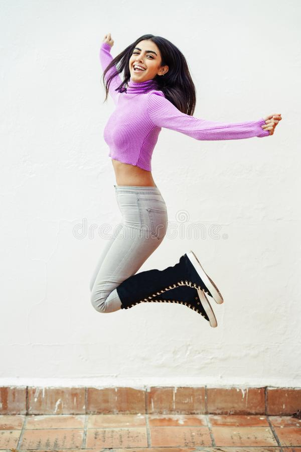 Happy persian woman jumping outdoors on white wall royalty free stock image