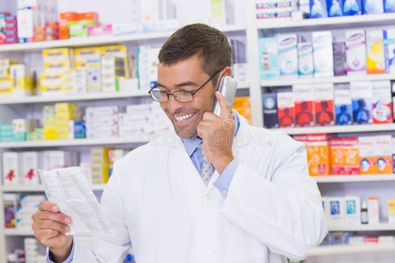Happy pharmacist on the phone stock image