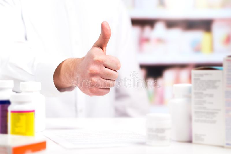 Happy pharmacist showing thumbs up at pharmacy counter. Full of medicine. Drugstore shelves in the background. Positive and cheerful druggist. Good or great royalty free stock photos