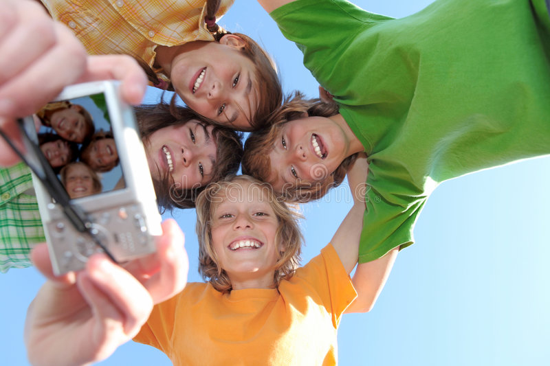 Happy photo camera. Happy smiling group of kids, children youth or teens with camera taking photo at summer camp