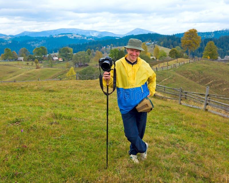 Happy photographer on autumn mountain background stock image