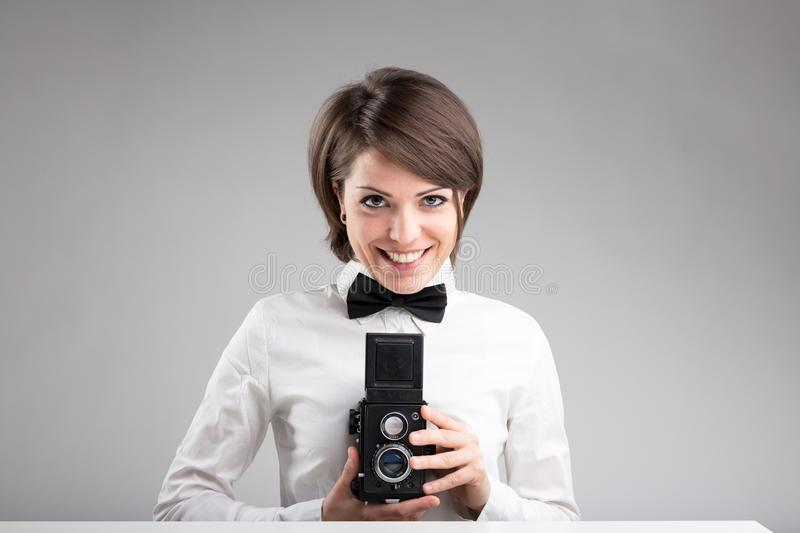 Happy photographer in bow tie. With a vintage twin-lens reflex camera stock images