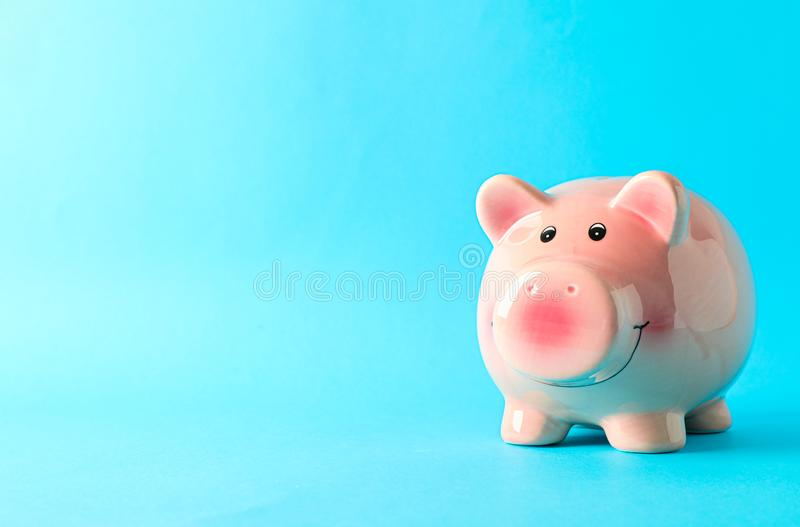 Happy piggy bank on color background, space for text. Finance, saving money stock photo