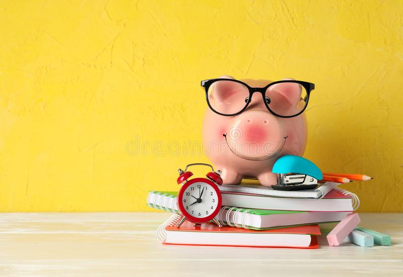 Happy piggy bank with glasses, and school accessories on white wooden table against color background, space for text royalty free stock photo