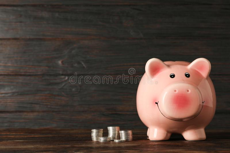 Happy piggy bank with money on wood table against wooden background, space for text. Finance, saving money royalty free stock photography