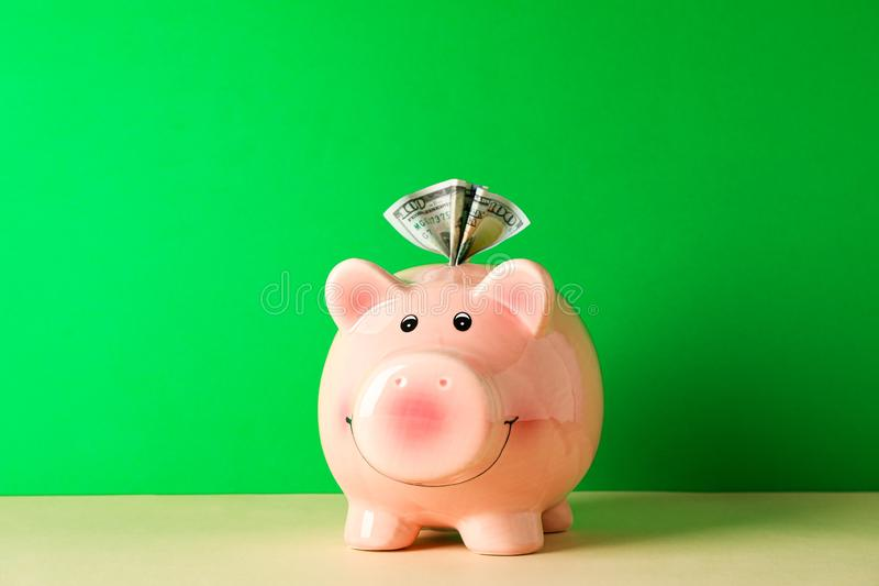 Happy piggy bank with one hundred dollar on color table against green background, space for text. Finance, saving money stock photos