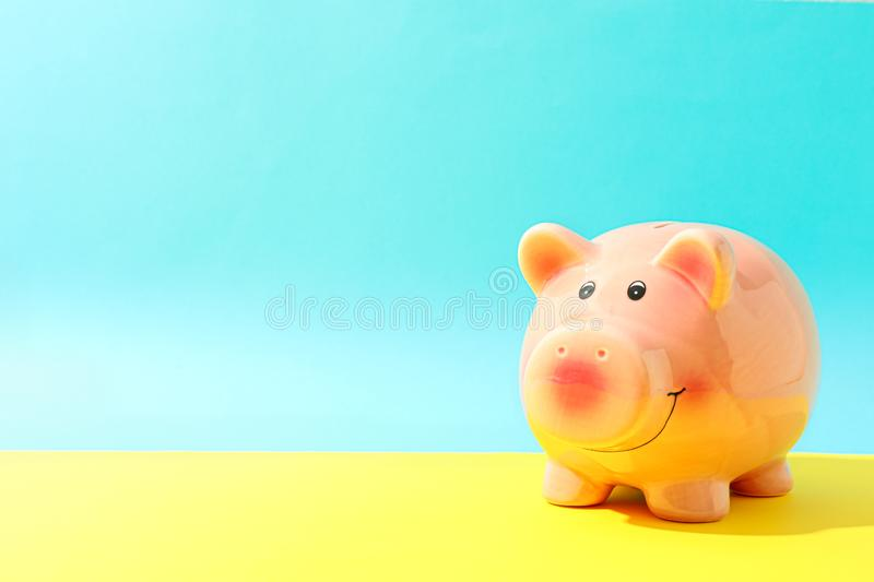 Happy piggy bank on yellow table against color background, space for text. Finance, saving money royalty free stock photos