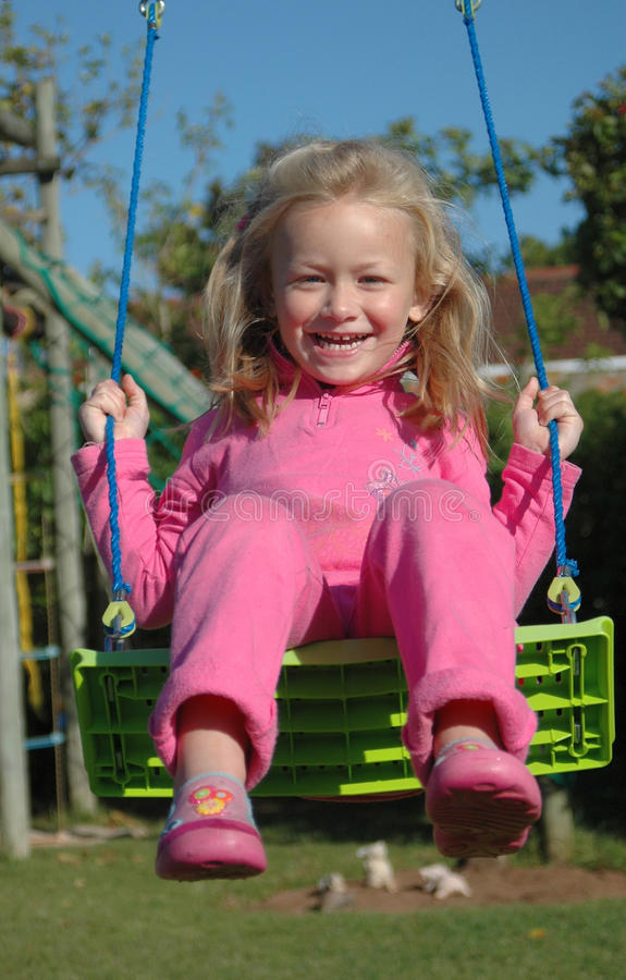 Happy child on swing. Cute little Caucasian girl child dressed in pink with happy laughing facial expression swinging on the playground outdoors stock photo