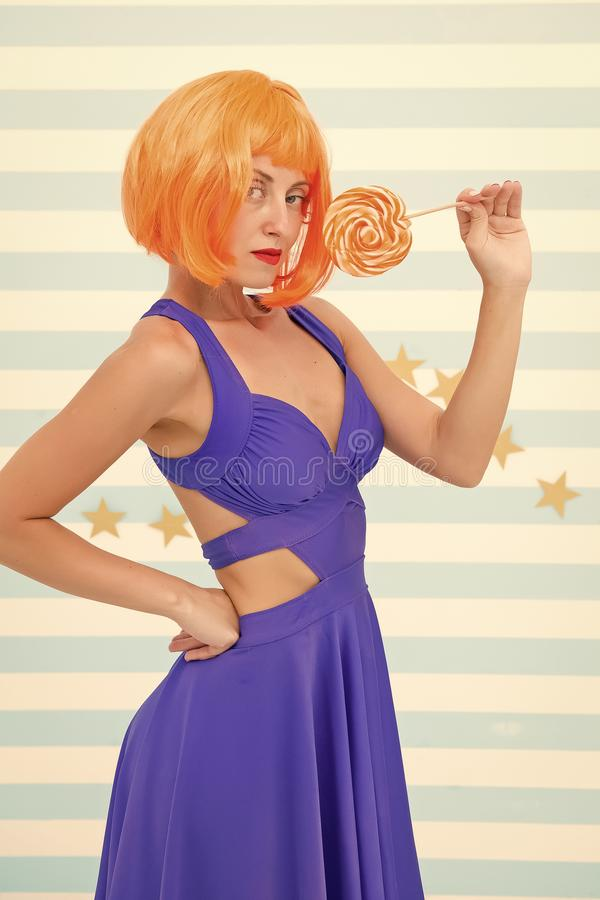 Happy pinup model with lollipop. Cool girl with lollipop. Sexy woman. Fashion girl with orange hair having fun. Crazy. Girl in playful mood. So much fun royalty free stock photo