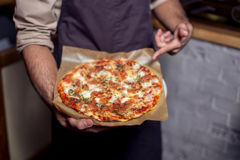 Happy pizza delivery man showing fresh pizza in a commercial kitchen.  royalty free stock image