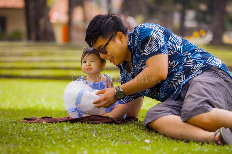 Happy playful Asian Chinese man as loving father enjoying sweet and beautiful baby girl daughter sitting together playing on grass stock photography