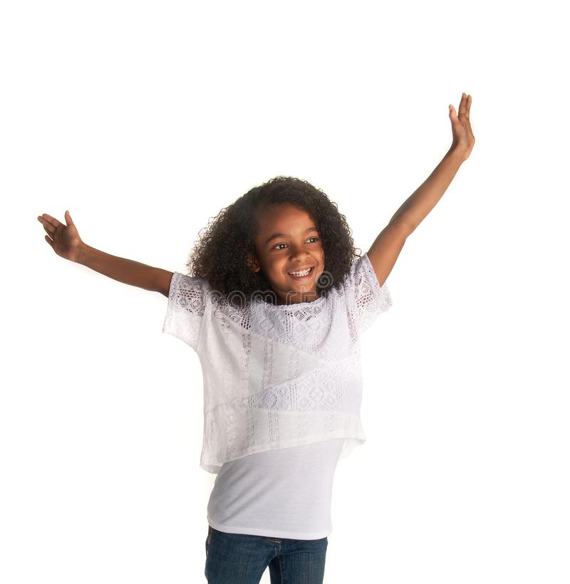Happy playful child holding arms aloft. Isolated against white stock images