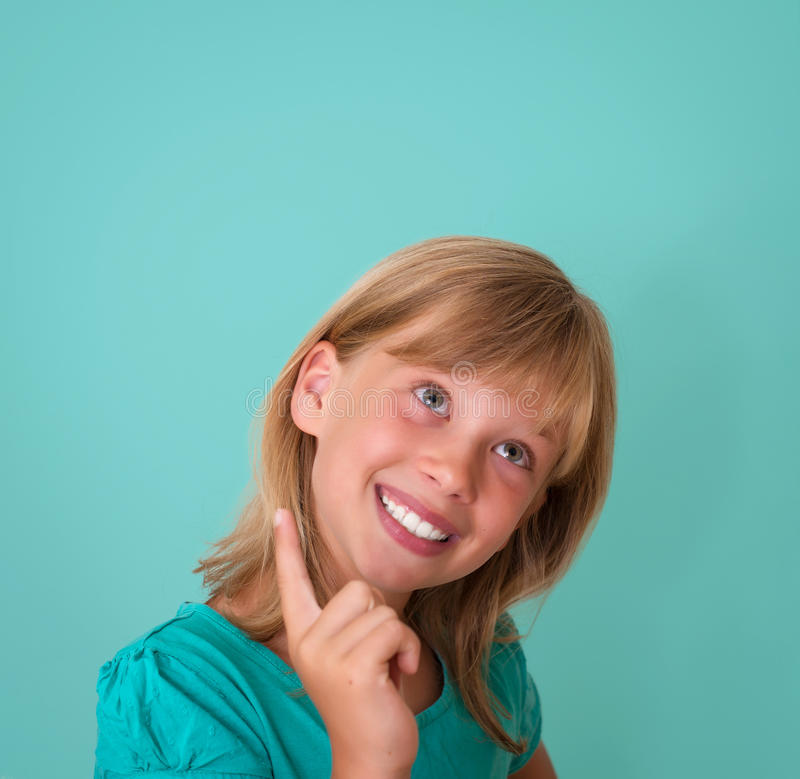Happy playful child smiling happy and joyful on turquoise background. Thinking beautiful girl looking to the side stock images