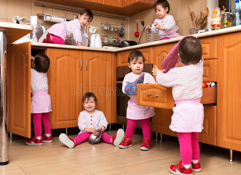 Happy playful girl playing in the kitchen stock photography