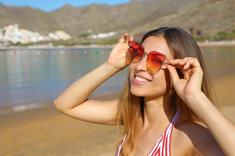Happy playful girl with sunglasses on the beach royalty free stock image