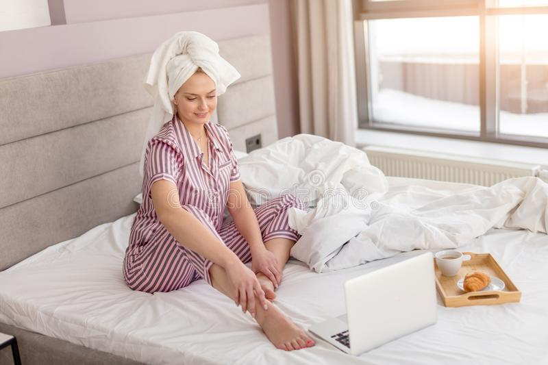 Happy pleasant housewife working on a laptop sitting on the bed in at home royalty free stock image